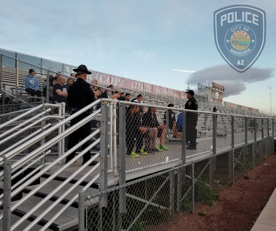 Picture of applicants sitting in the stands, being talked to by Sgt. Perez.