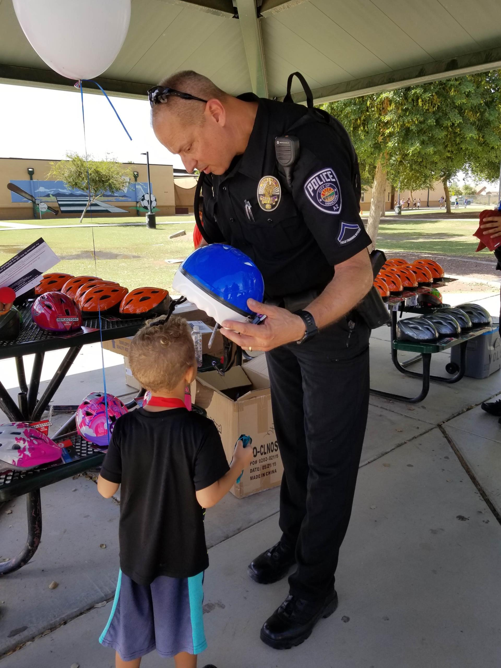 Ofc Torres fitting a bike helmet at Kids Day 2018