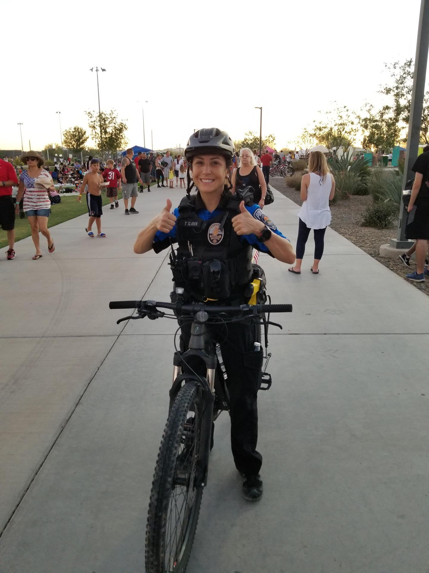 Picture of Officer Slider on her bike, showing Thumbs Up with both hands.